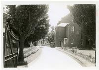 Driveway, front gates and school bus. c 1940